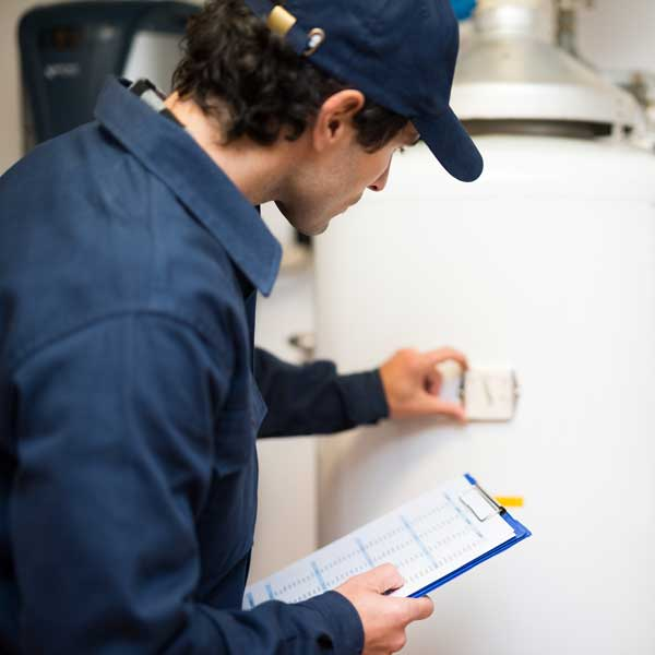 technician repairing hot water heater